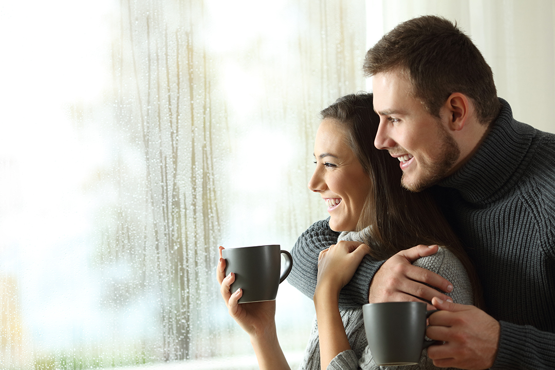 happy couple looking out window after storm restoration